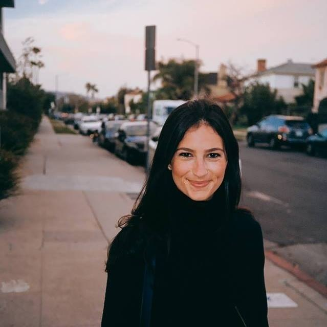 Melissa Oppenheim Lano stands outside on a neighborhood street, smiling at the camera. She has long black hair and is wearing a black turtleneck.