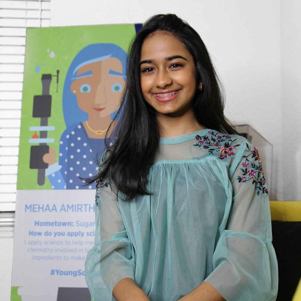 Mehaa Raja Amirthalingam stands smiling at the camera. She has long black hair and is wearing a turquoise blouse with embroidered flowers on the shoulder.