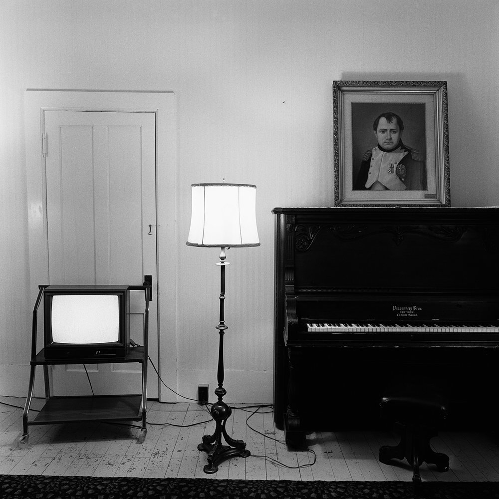 "7. Television, Lamp and Spirit Painting of Napoleon, Maplewood Hotel. Lily Dale. 1993. Toned Gelatin Silver Print. 15""X15""."