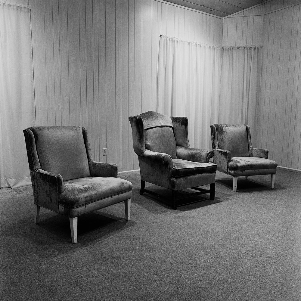 """21. Chairs, Auditorium Stage. Lily Dale. 1993. Toned Gelatin Silver Print. 15""""X15""""."""