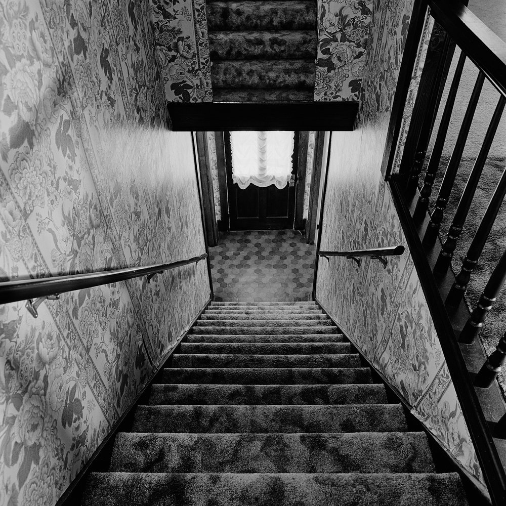 "26. Staircase and Mirror, Buchanan House. Lily Dale. 1996. Toned Gelatin Silver Print. 15""X15""."