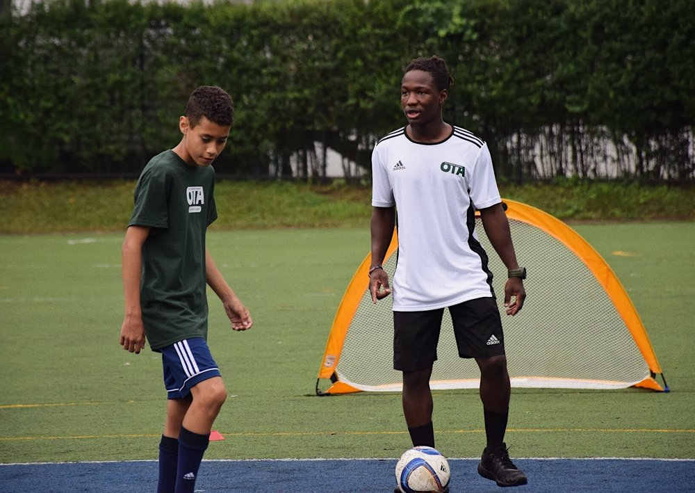 Meet Coach Des - Coach Des was born in Freetown, Sierra Leone where he first gained his love for soccer. While growing up in Montclair, he continued pursuing his passion as he was a member of both the volleyball and soccer programs at Montclair High School. After graduating high school in 2012, Des began his coaching career as a volleyball coach, it was not until 2 years later that he began coaching soccer. Des started working for Montclair United in 2014 where he dedicated hours of his time to learning and studying the proper trades needed to become a quality grassroots soccer coach. Within a year, he created a coaching style of his own that caught the attention of SDFC/SDA owner Ashley Hammond, who employed Des in his company. Now that Des started his own company, Our Training Academy, Ash is still a key mentor is Des's coaching career.Des's long-term youth development goal is that all players leave each session with an OTA coach knowing that they have better techniques that they can display on the field.Our goal is to help players become overall better individuals by having them learn to be held accountable as well as understanding the importance of positive decision-making skills so that they can mature onto the next level.
