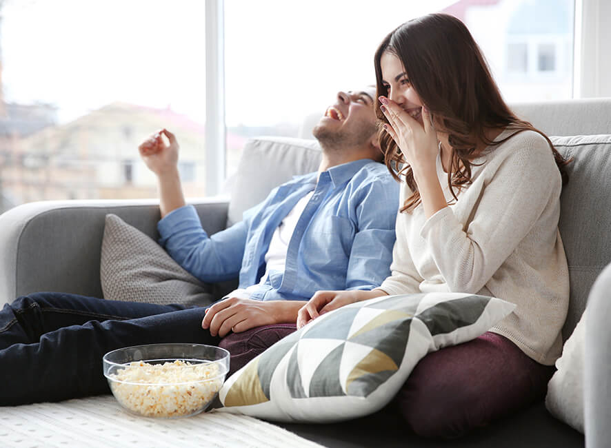 Meaningful location - couple having popcorn and laughing on couch.jpg