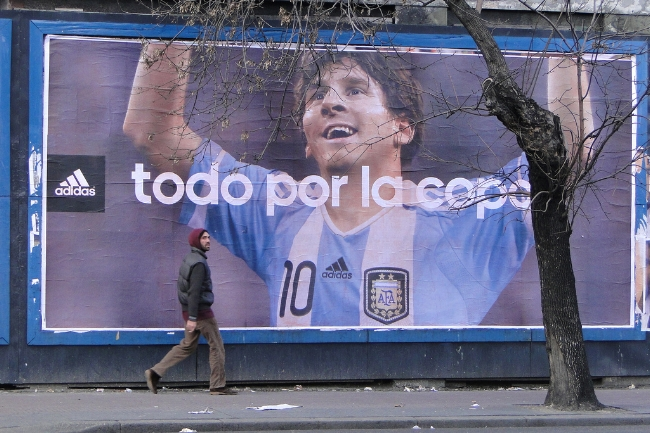 A man walks by a poster of Lionel Messi in Buenos Aires, 2011. Foto: Adam Jones/Flickr; Source: OCCRP