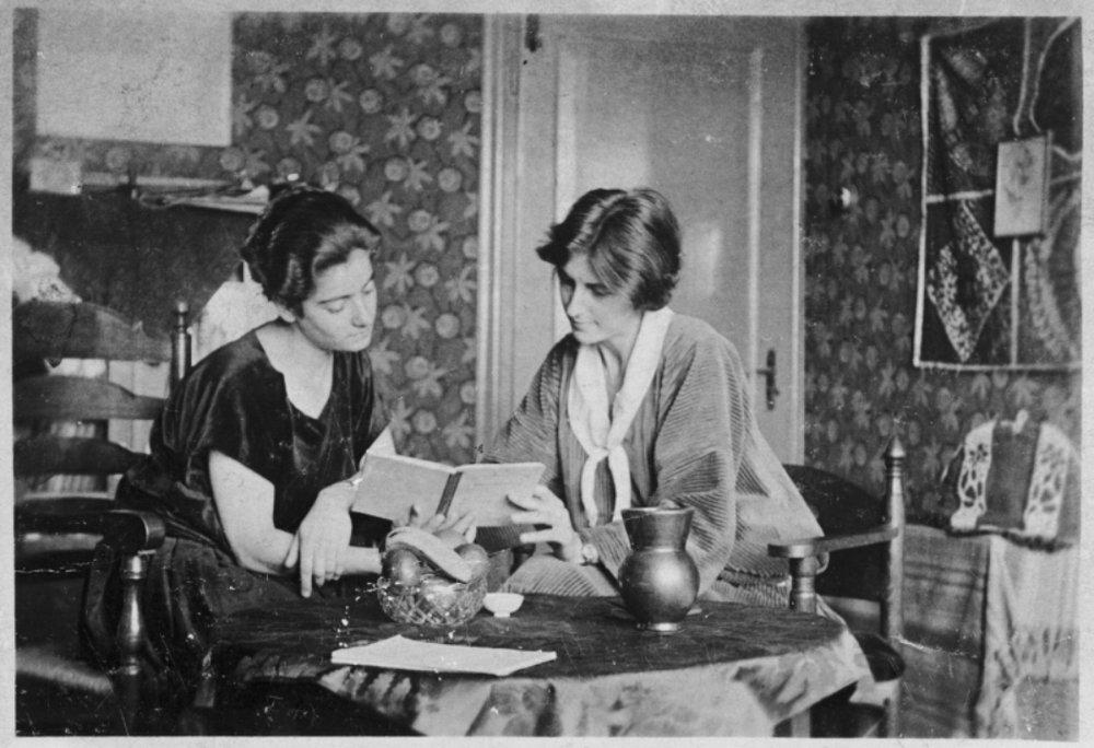Frieda Belinfante (links) aan tafel met haar partner componiste/pianiste Henriëtte Bosmans in hun huis aan de Hendrik Jacobszstraat in Amsterdam, ca. 1927 - 1929.
