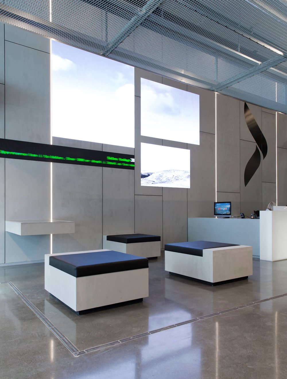 Referanseprosjekt: Elkjøps hovedkontor i Nydalen med Panbeton, Classic by Studio LCDA på vegg, tak og møbler med logo og skjermer innfelt.