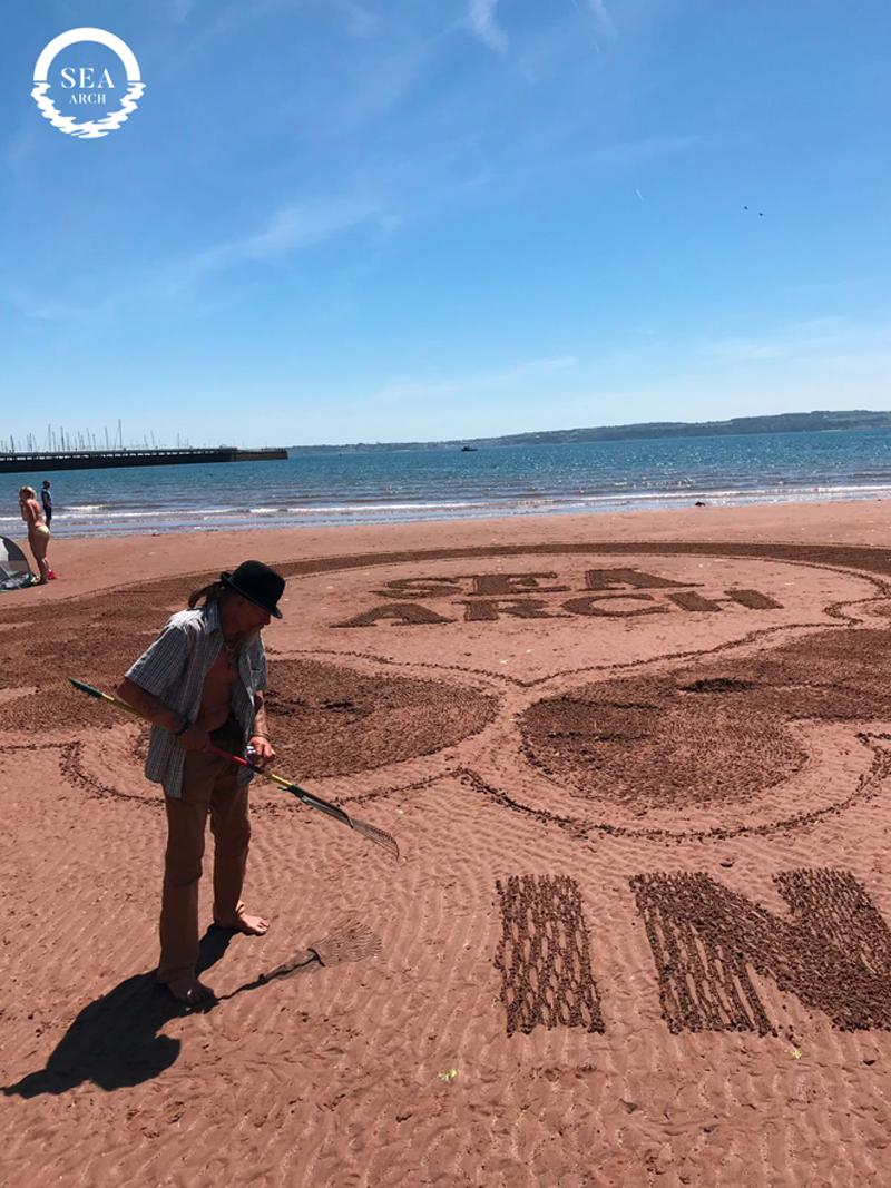 Sandman creating Sea Arch logo in sand
