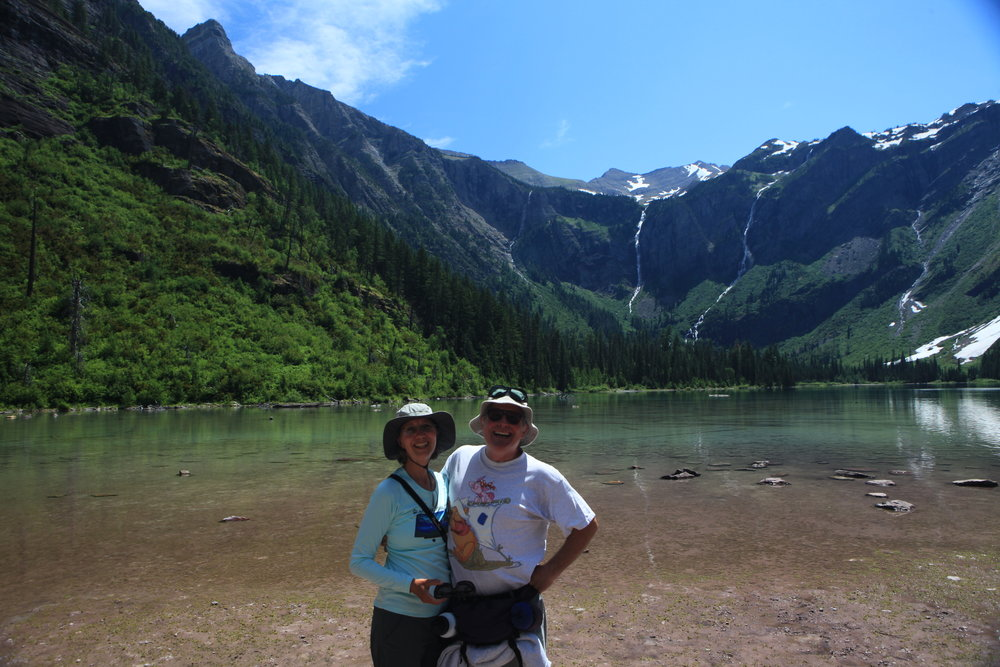 Me enjoying life again. My husband joins me at Avalanche Lake in Glacier NP. This shows my adapted hiking hat with flaps up.