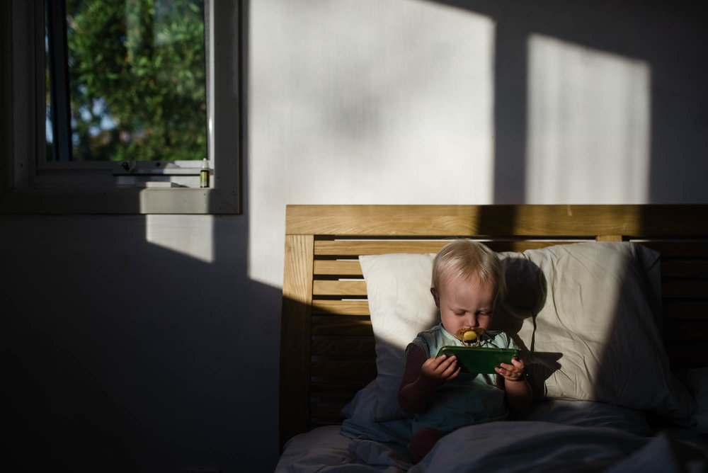 learning_photography_toddler_watching_phone_in_bed-1.jpg