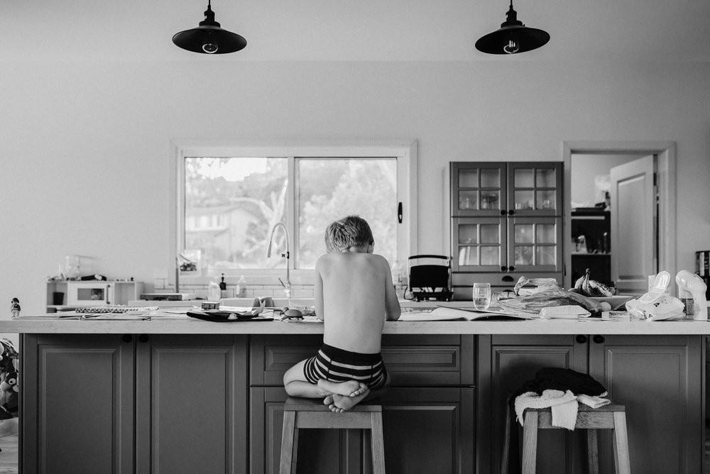 black_and_white_image_of_the_back_of_a_boy_sitting_on_his_feet_at_the_kitchen_counter.jpg