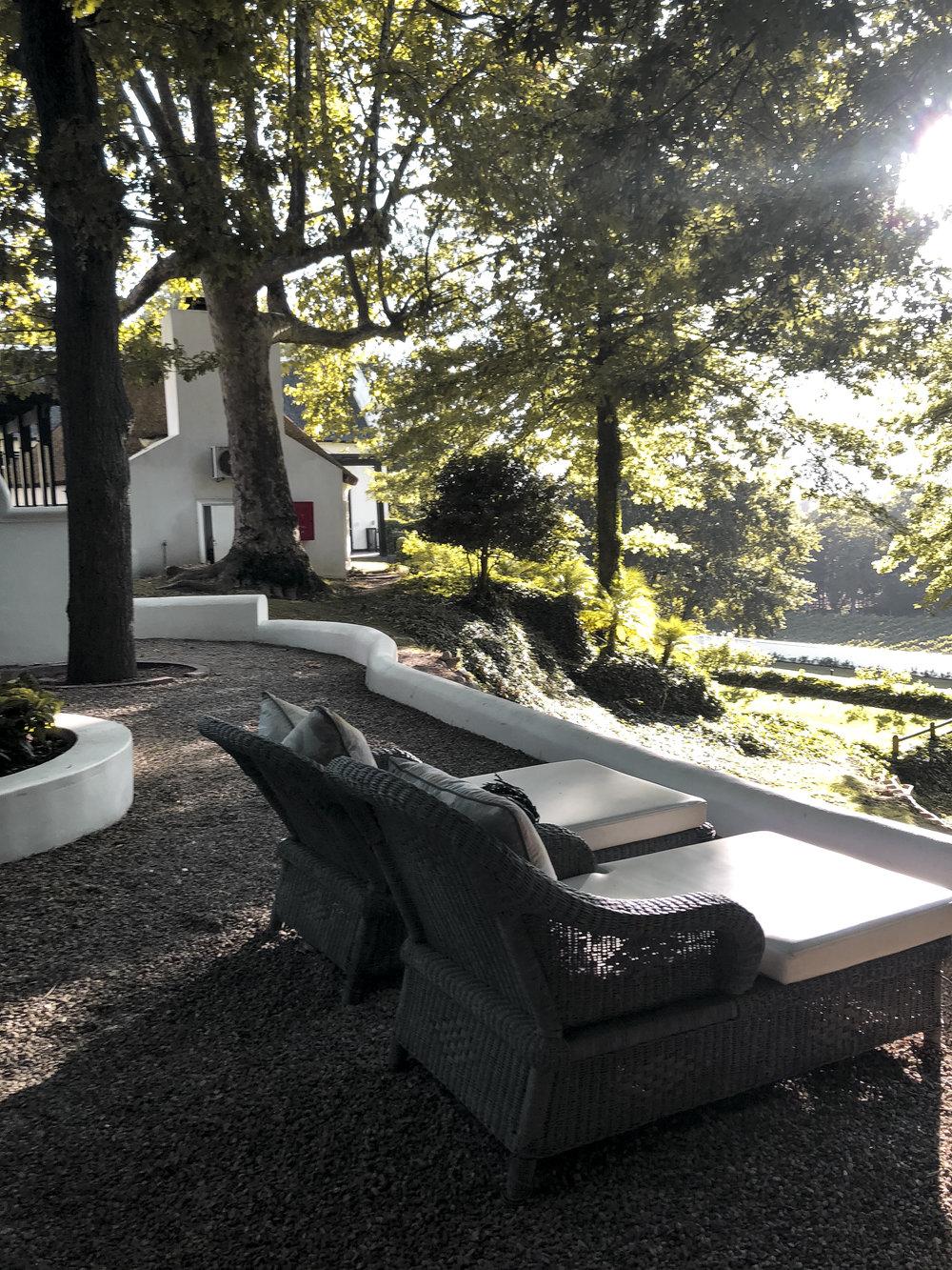 Mitten in der Natur - Rundherum befindet sich Natur pur, sogar eine eigene kleine Terasse ist dabei. Das Zimmer ist modern afrikanisch eingerichtet, am Bettende steht ein Kamin und von der Badewanne aus hat man einen Blick auf das Weingut.