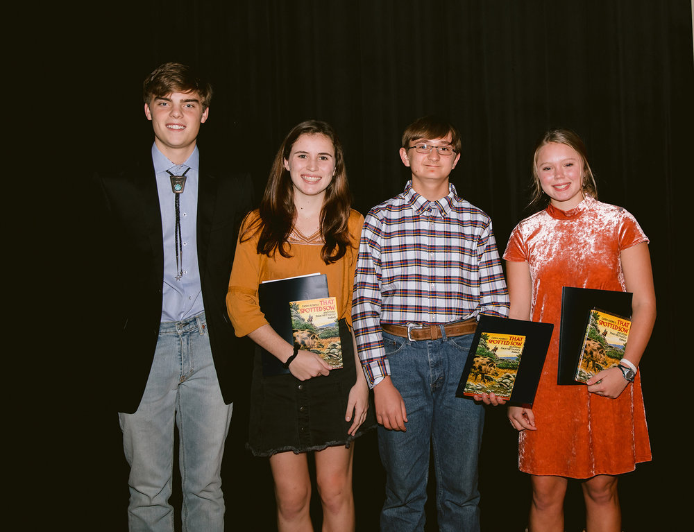 The winners of the 2018 Youth Writing Competition! Benjamin Ashley presents the Carlos Ashley Memorial Writing Award to Susanna Harpold, Mark Millhouse and Sadie Eidson