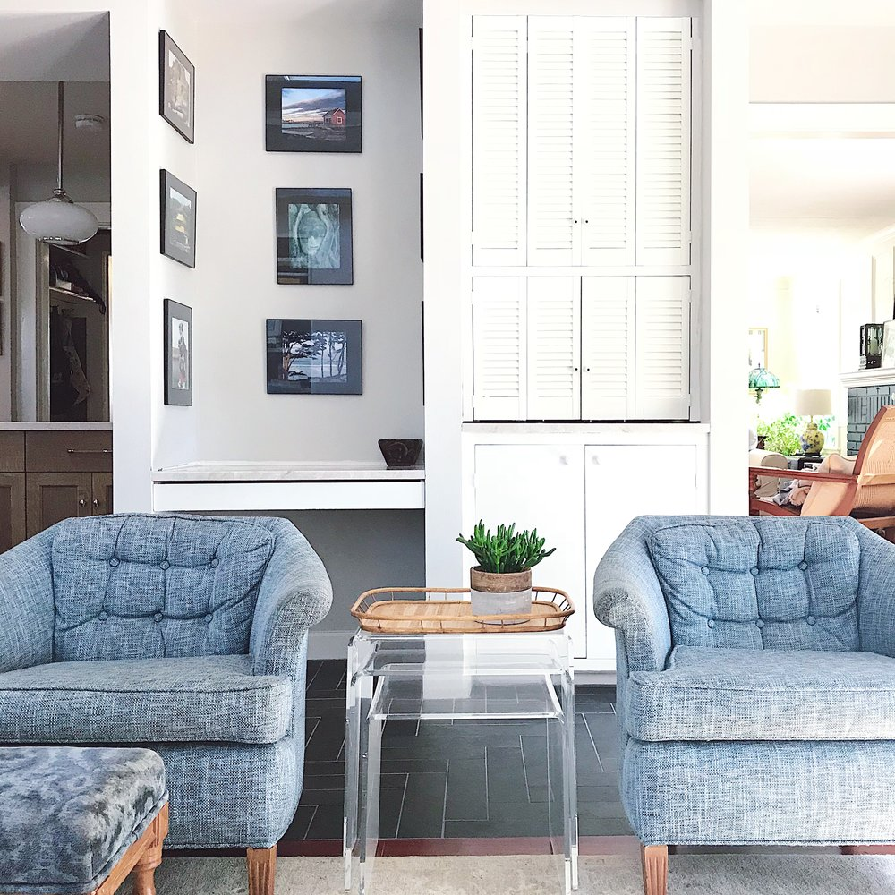 A pair of vintage club chairs Jen found for a song at an estate sale and had reupholstered. The lucite nesting tables and woven tray are other estate sale finds.