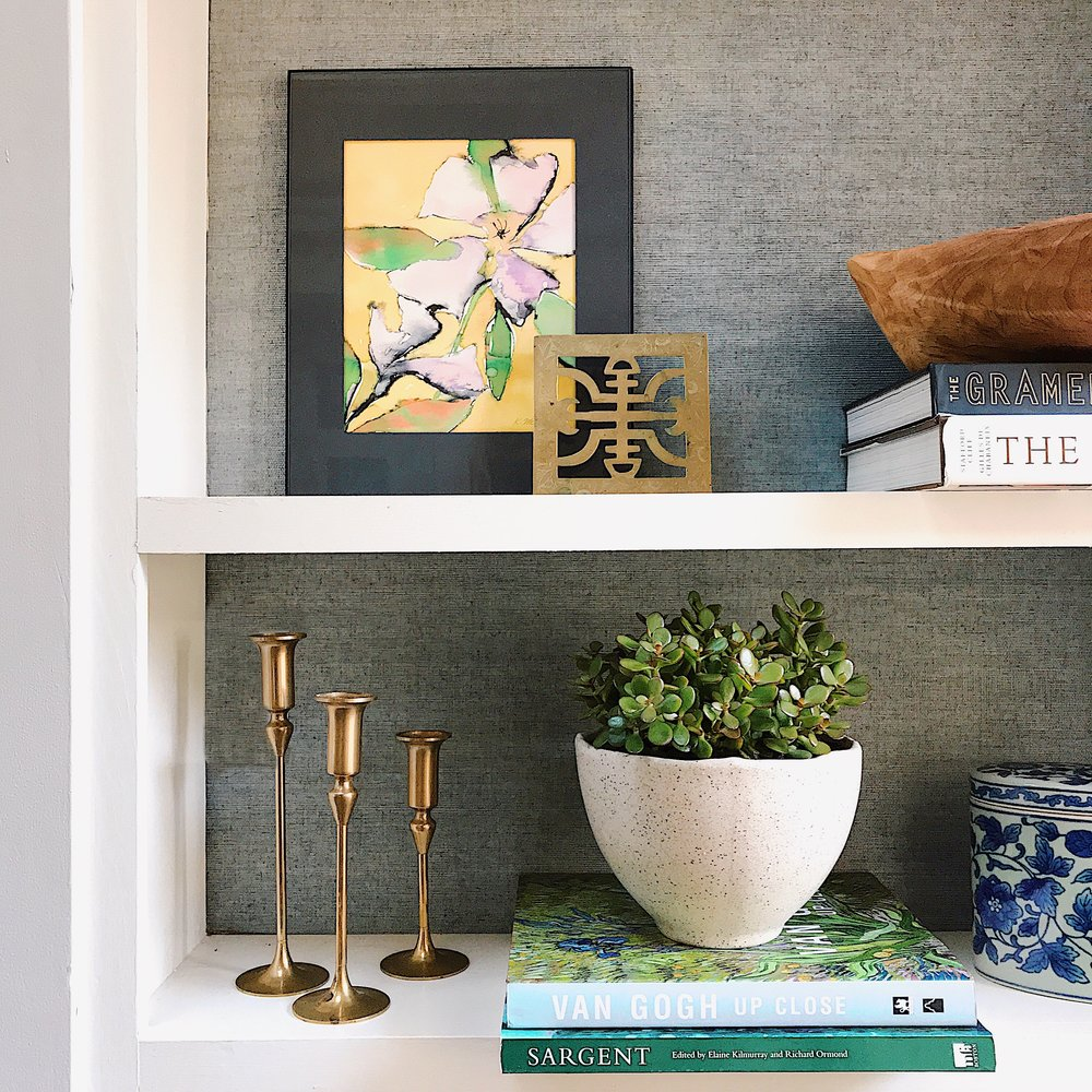 Coffee table books are great for book shelf styling (as are brass candle sticks, trivets, and porcelain tea caddies)