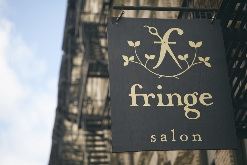 Fringe Salon NY on Manhattans Lower East Side. Boutique hair salon for lived in hair styles and balayage LES. Our black sign with gold logo. Woman-owned business in NYC for balayage NY, natural looking Ombre hair NYC.