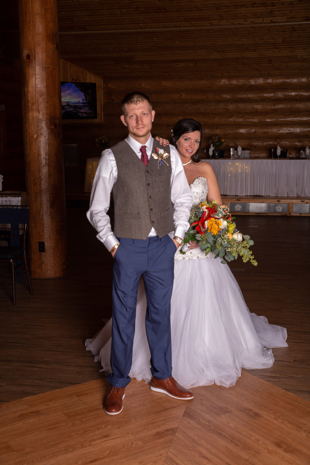 Glenhaven winter Minnesota wedding rustic barn, orange and yellow bouquet, groom in vest and navy pants