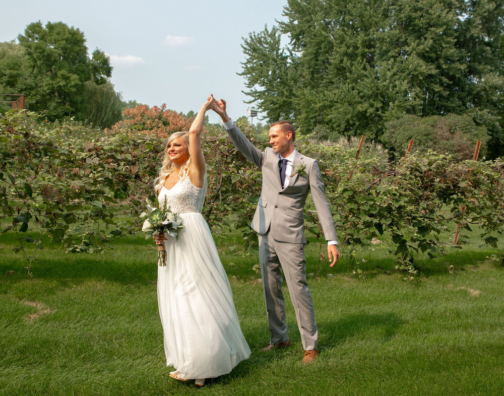 Cindyrellas Garden outdoor wedding ceremony by a private lake with wooded backdrops, twirl