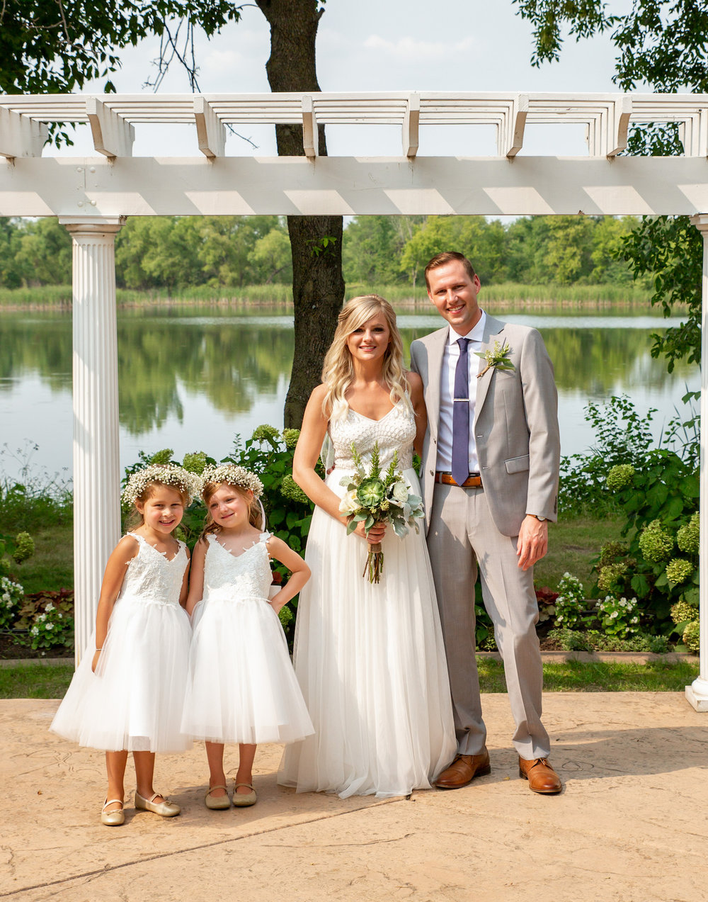 Cindyrellas Garden outdoor wedding ceremony by a private lake with wooded backdrops, flower girls in white with floral crowns