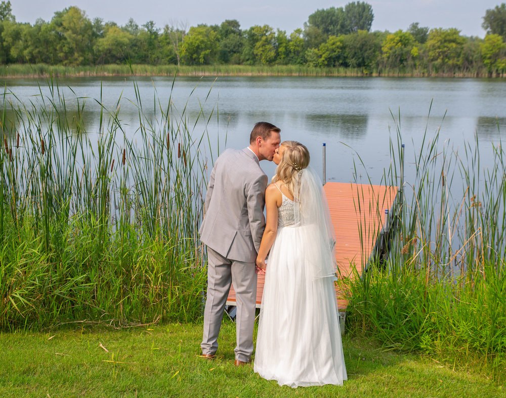 Cindyrellas Garden outdoor wedding ceremony by a private lake with wooded backdrops, dock photo
