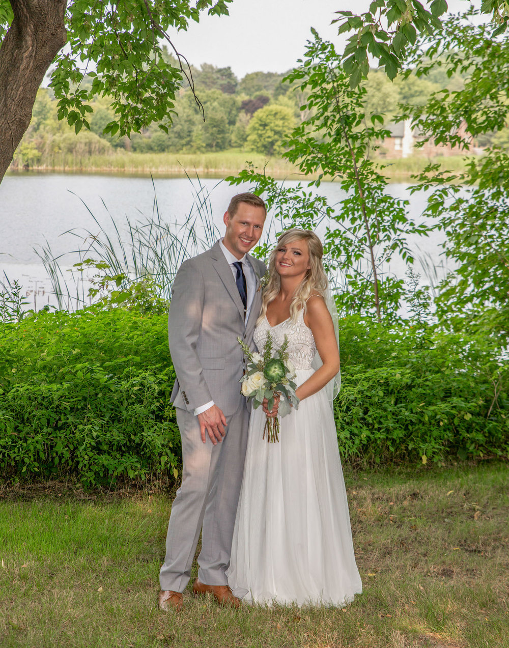 Cindyrellas Garden outdoor wedding ceremony by a private lake with wooded backdrops, lake in the backdrop
