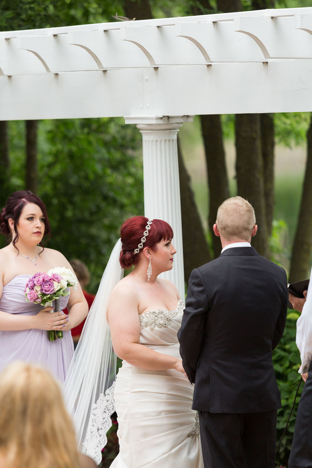 Cindyrella's Garden outdoor ceremony by the lake with a redhead bride, lavender bridesmaids