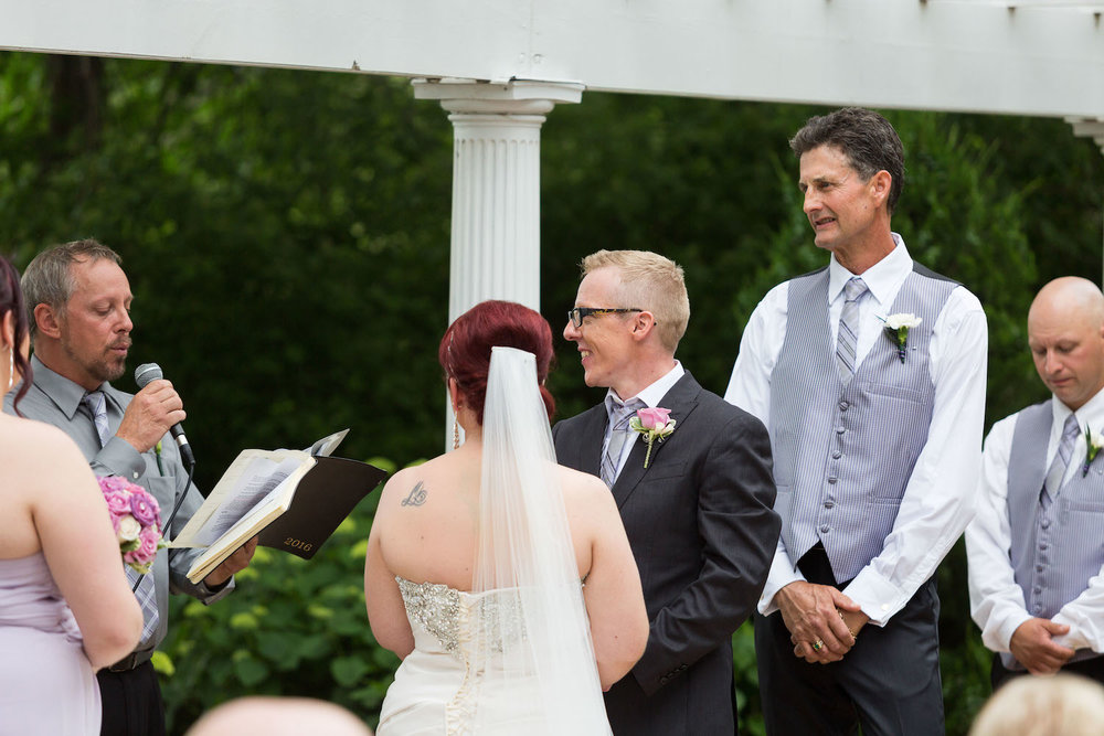 Cindyrella's Garden outdoor ceremony by the lake with a redhead bride, grey vest