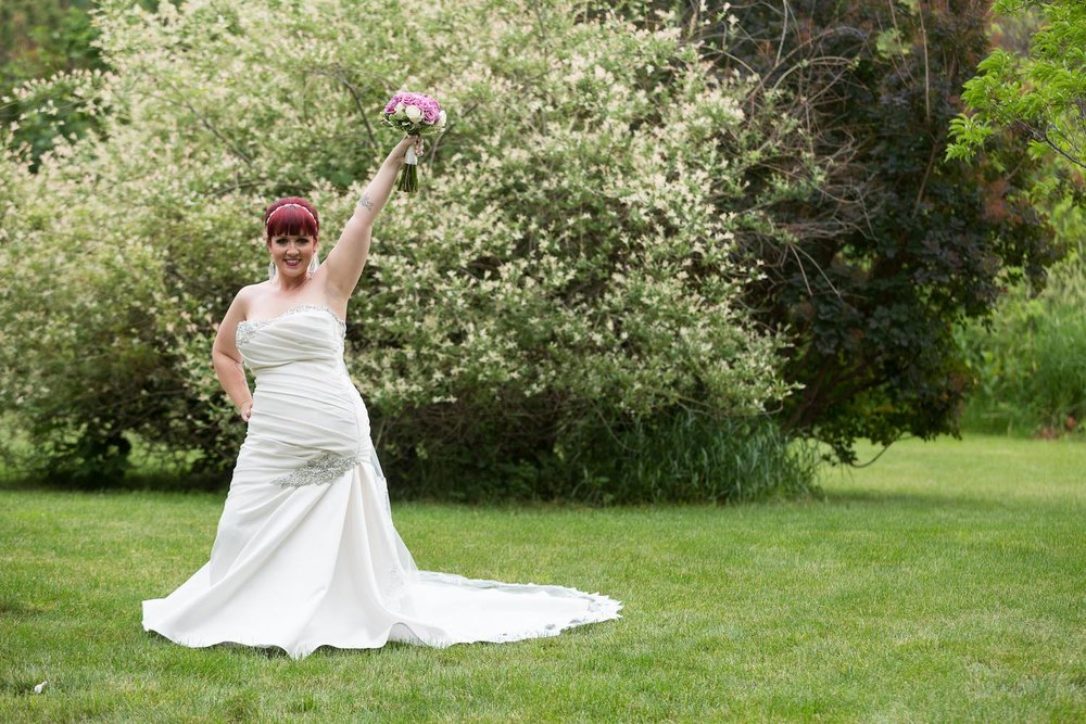 Cindyrella's Garden outdoor ceremony by the lake with a redhead bride, celebration pose