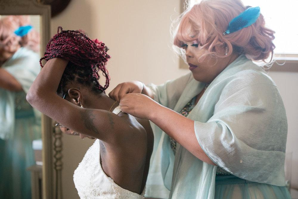 Mom helping her daughter get into her dress   Danielle Albrecht fab wedding photographer in Minnesota