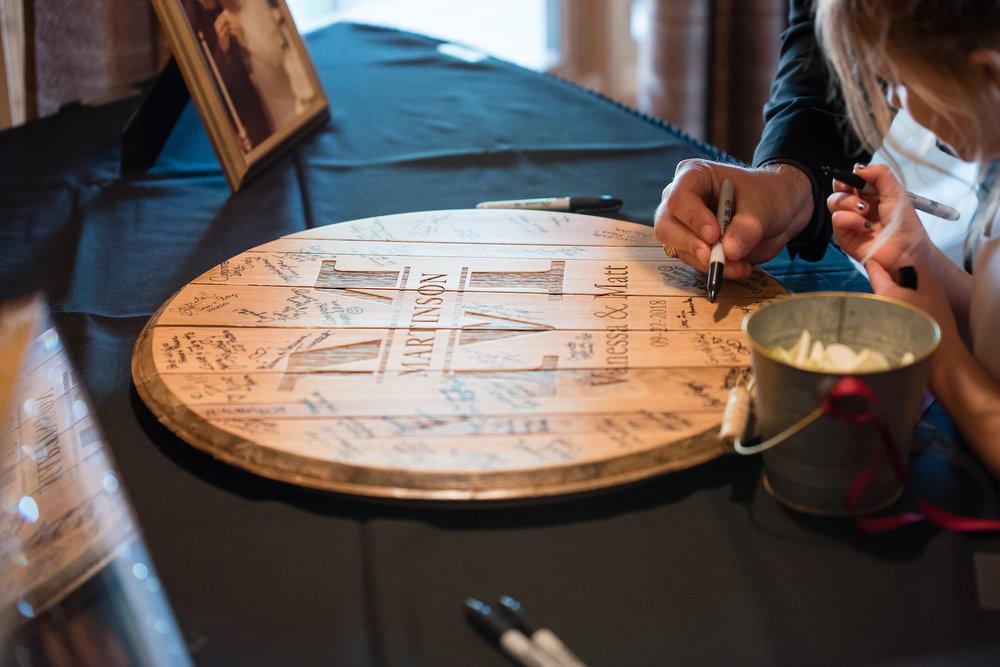 Danielle Albrecht photographer at rustic Farmington lodge inspired wedding | wood monogram guest book