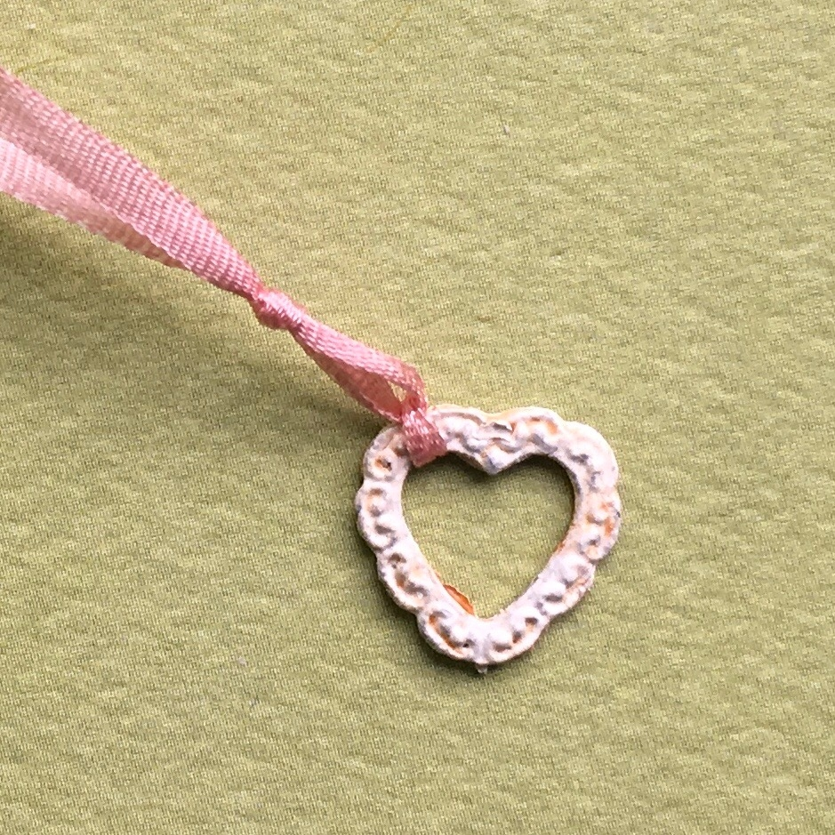 Painted metal heart frame tied with ribbon