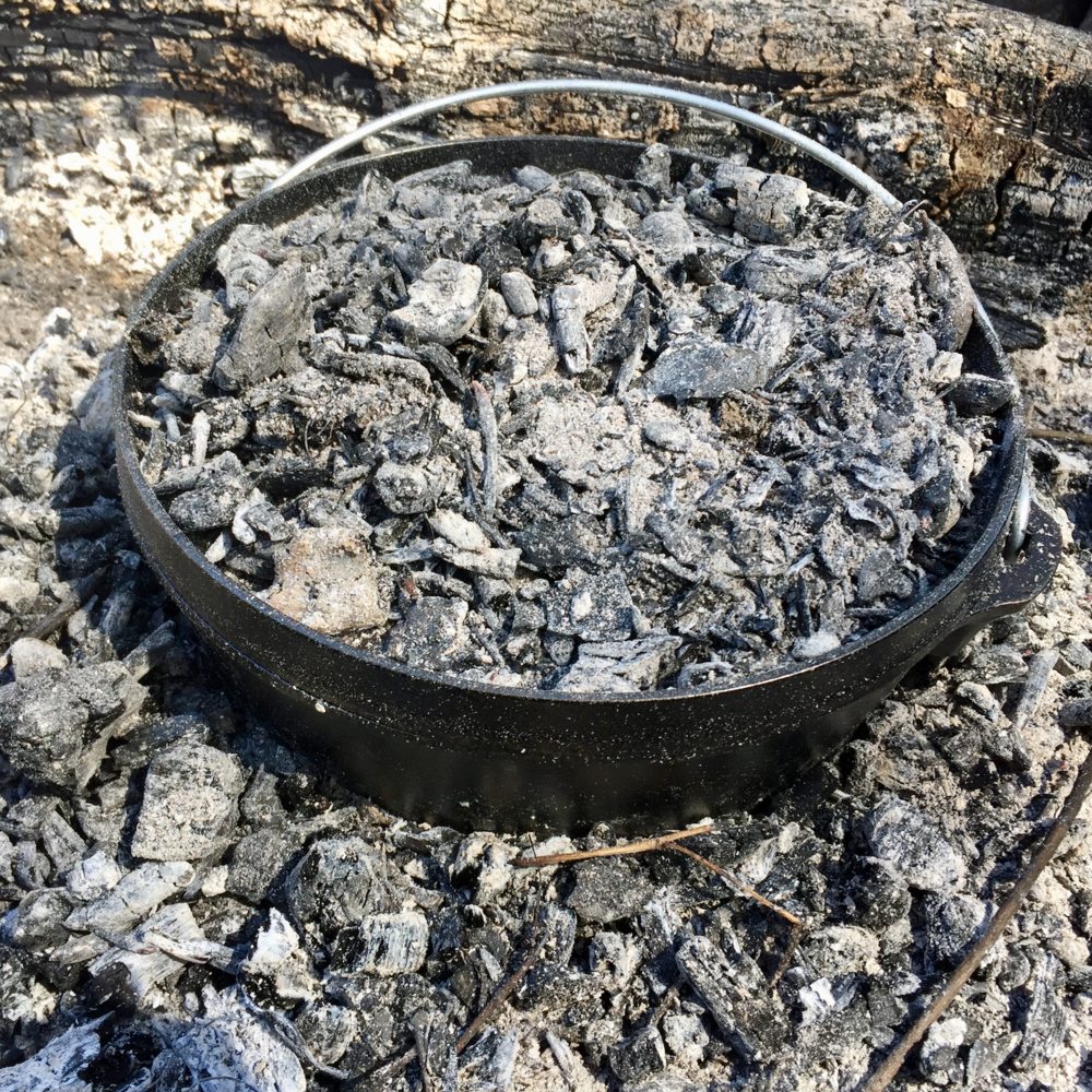 A very specialized  Dutch oven for outdoor cooking . This one has feet for setting into a bed of coals and a rimmed lid for holding coals on top. Outdoor cooking Dutch ovens are also highly versatile; because you can heat the top and the bottom of the oven, you can use it to bake.