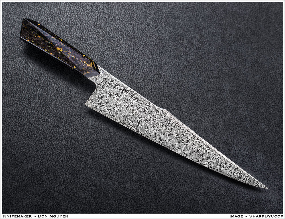 "'Hostile Kitchen'  Type: Gyuto (Japanese style chef's knife)  Blade Length: 270mm (10.60"")  Overall Length: 406mm (16.00"")  Blade Material: Damasteel's Odin Heim pattern (RWL24 and PMC27)  Handle Material: Shredded carbon fiber with extra gold powder by Composite Craft, brass pins, and black G10 liners  Pricing on similar knife: $3500"