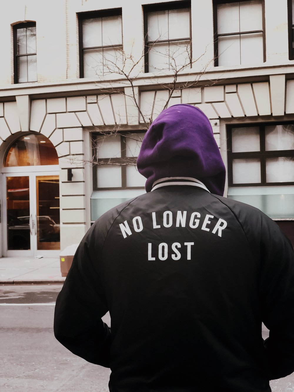 "Image: Person with back turned in a jacket with ""No Longer Lost"" on the back in text. Photo by  Jon Tyson  on  Unsplash"