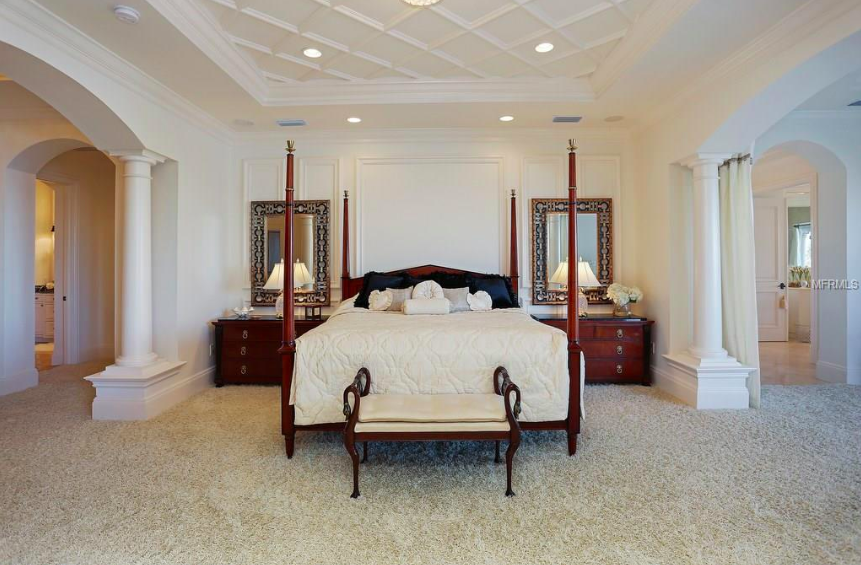 The master suite is spacious and overlooks sparkling waters, with his and hers bathrooms and high, custom ceilings.