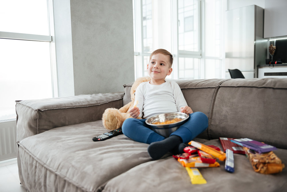 graphicstock-picture-of-smiling-boy-on-sofa-with-teddy-bear-at-home-watching-tv-while-eating-chips-holding-remote-control_BunRZ_Fpl.jpg
