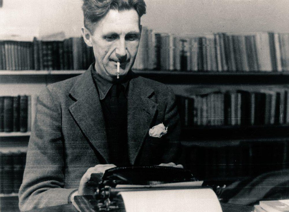 George Orwell sits at a typewriter with a cigarette in his mouth and a bookshelf in the background.