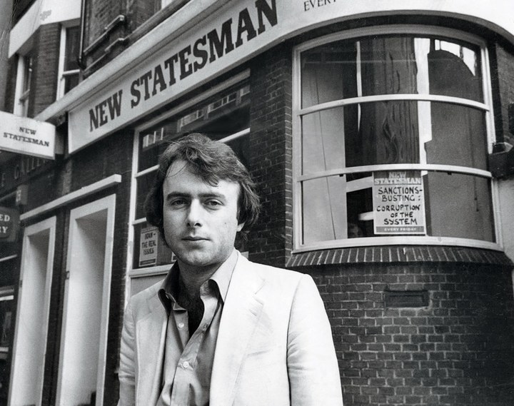 A young Christopher Hitchens, dressed in a light-coloured suit, stands outside the offices of New Statesman magazine in 1970s London
