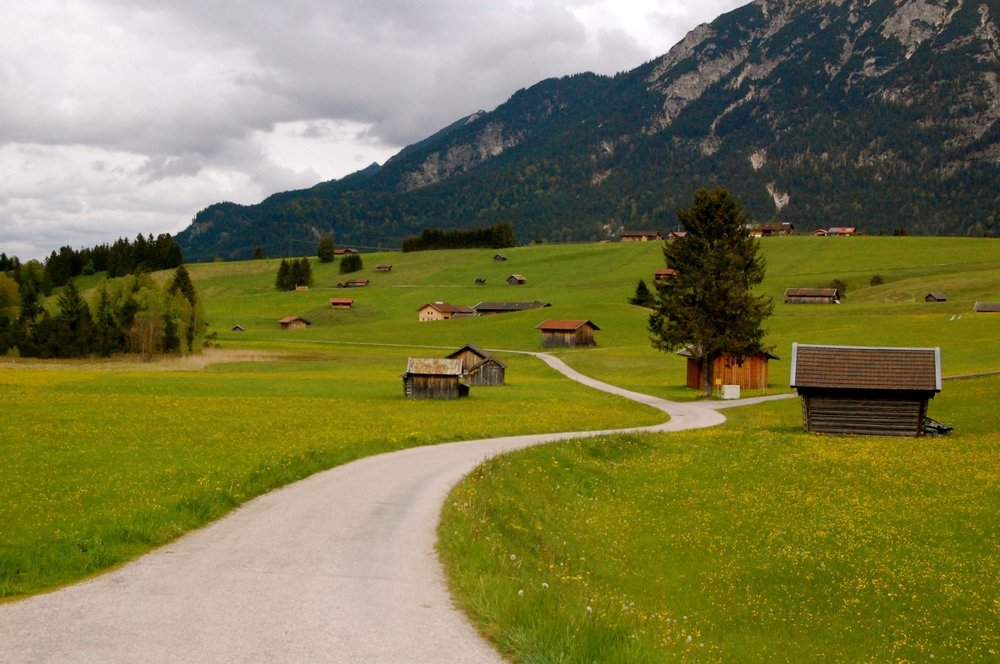 A country lane winds its way through daisy-spangled fields and little wooden farm sheds near Mittenwald, Germany