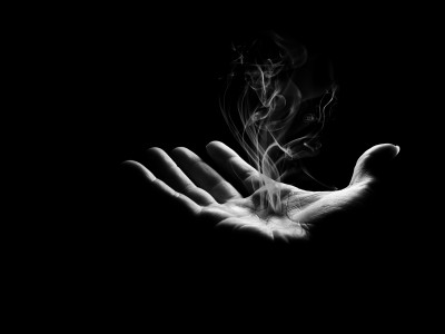 Smoke rises moodily from an otherwise empty and outstretched hand