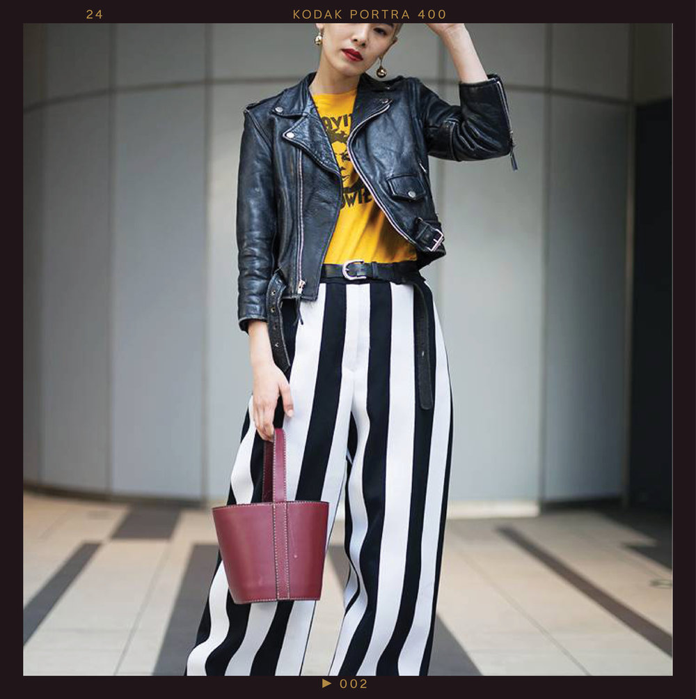 This bold outfit features two of Tokyo's big trends— oversize bottoms  with wide-leg striped pants and  pops of primary colors , and yellow graphic T-shirts balanced out by a bold red lip and matching heels.
