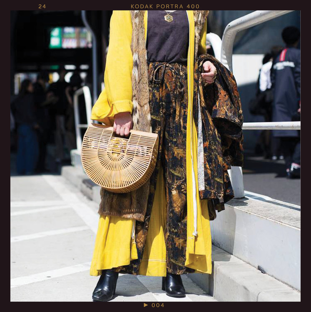 """It would be an understatement to reduce this floor-length canary yellow duster to a """" pop of primary color ."""" Paired with the  unexpected textures  of a fur under layer, a bamboo handbag, and bold statement jewelry, the only subtle part of the outfit is the  black leather boots ."""
