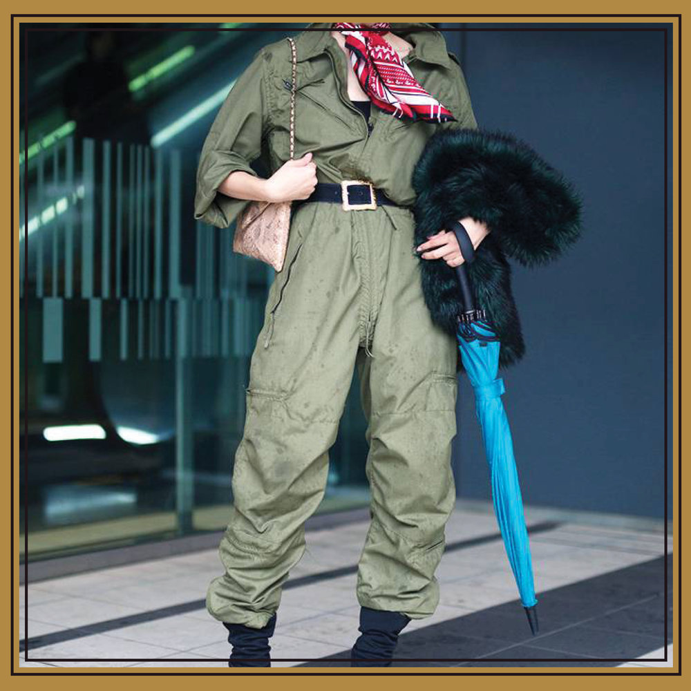 A true jumpsuit, the head-to-toe khaki look is livened up by a  pop of primary color  via the patterned silk scarf worn as a neckerchief. The jumpsuit's large fit is made chic with a black belt tied tightly at the waist and  oversize bottoms  tucked into  black satin ankle boots .