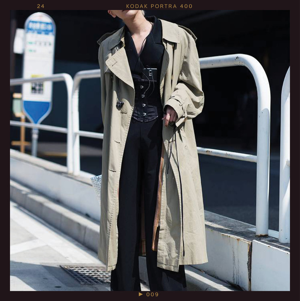 This ensemble exhibits the  oversize bottoms  trend and  plays with proportions . Wide-leg pants (worn extra long) and a blazer are unexpectedly cinched in at the waist with a matching black corset and topped off with an oversize trench coat.