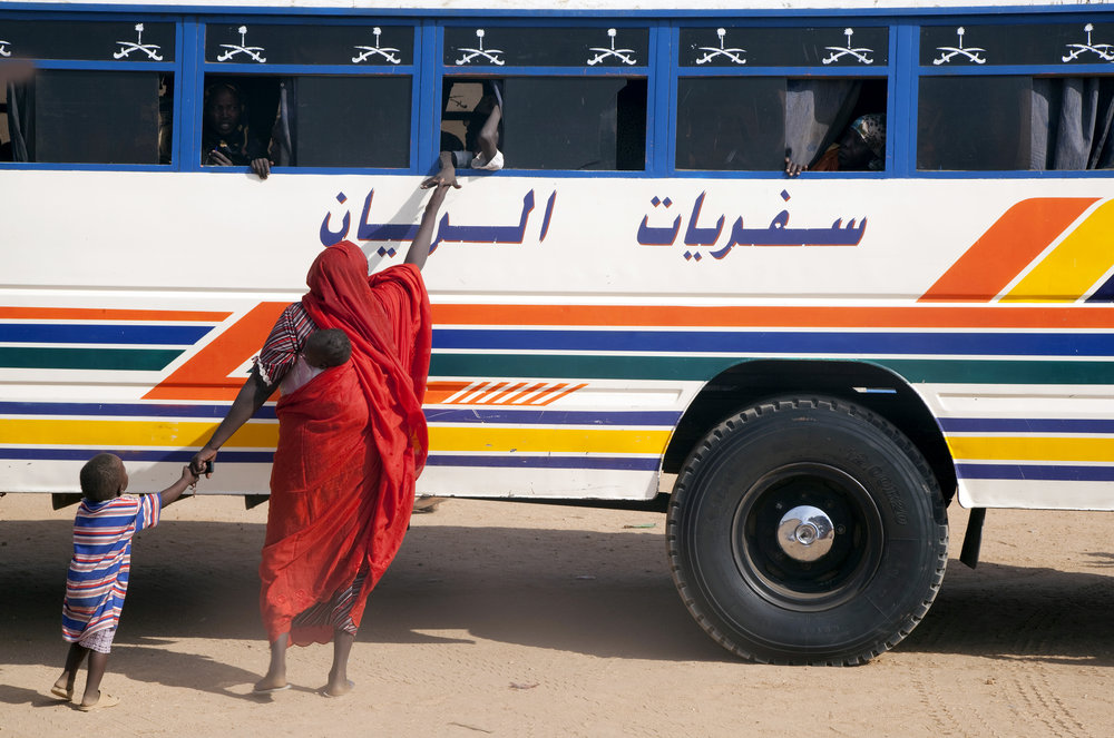 A displaced Sudanese woman says goodbye to a loved one aboard a bus leaving Kalma Internally Displaced Persons (IDP) Camp in Nyala, South Darfur. 07 December 2010 I Nyala, Sudan  © UN Photo/Albert González Farran
