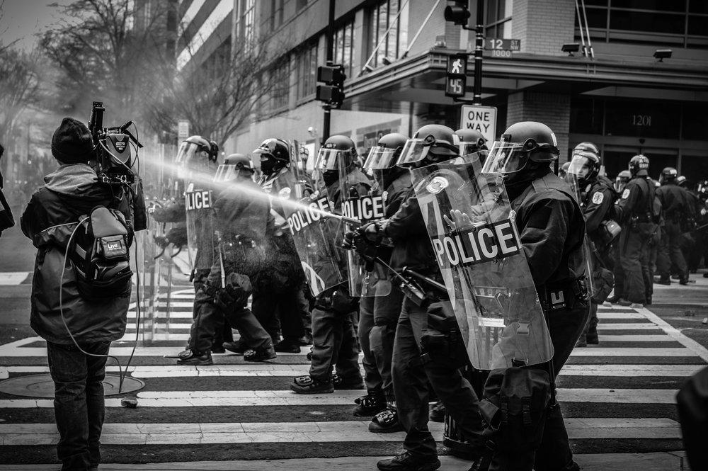 police riotgear spraying pedestrian.jpg
