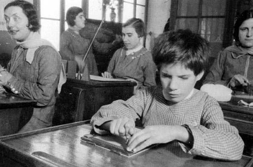 Jóvenes invidentes leyendo mapas en relieve y lectura en Braille en un Centro Asistencial para ciegos en plena guerra civil. 1936-1937