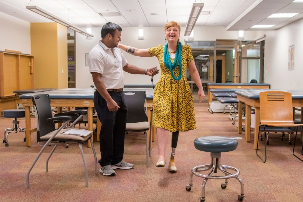 Shannon Jenkins, of Somerset, lets out a laugh while holding her balance with the aid of Chatham University physical therapy graduate student Brandon Maharaj. Maharaj was one of several physical therapists on hand to help evaluate women amputees.