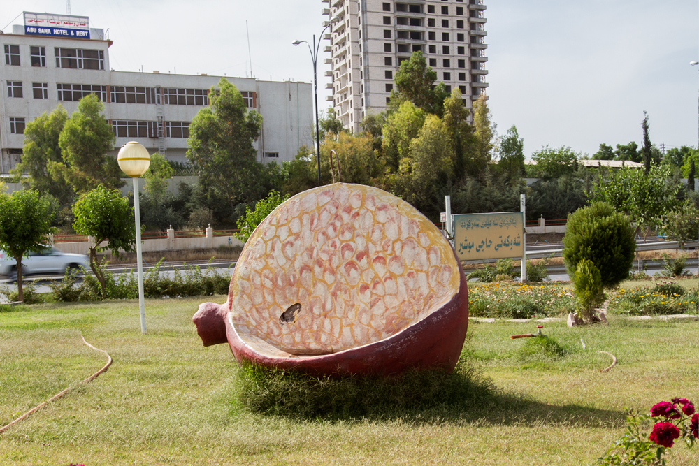 Molded benches honor crops including apples and pomegranates.