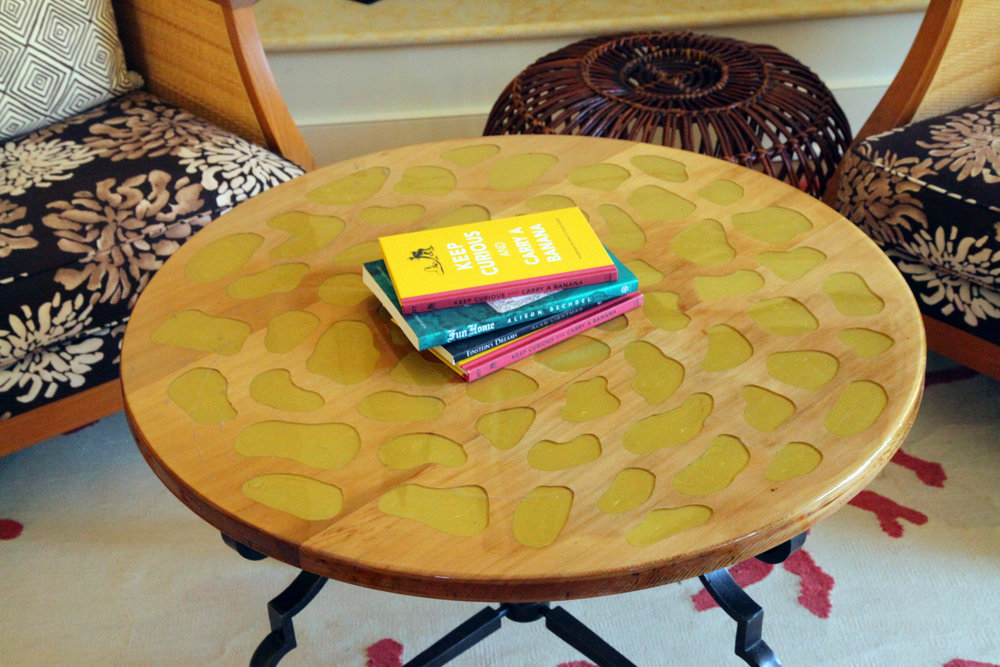 A discarded iron base becomes a stunning coffee table with solid wood and organically shaped golden resin insets