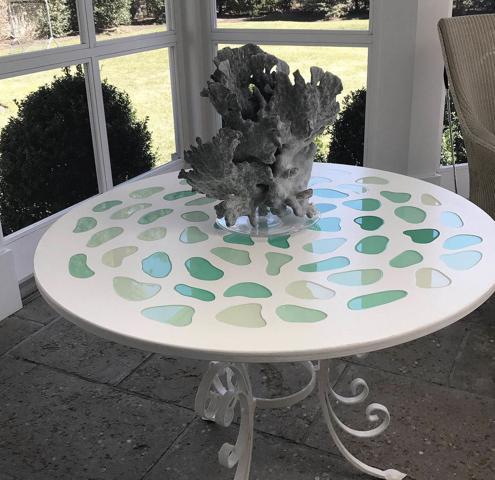 A discarded iron base transformed into a delightful poolside table with candy colored organic shaped resin insets